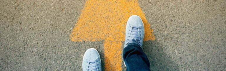 Füße schreiten in Richtung des Pfeils am Boden
